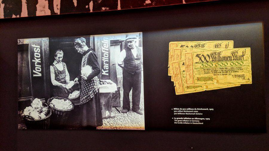 A display with old reichsmarks and a photo of a wheelbarrow full of banknotes