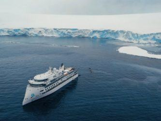 A luxury expedition cruise ship, The Greg Mortimer, floating near an ice laden shoreline