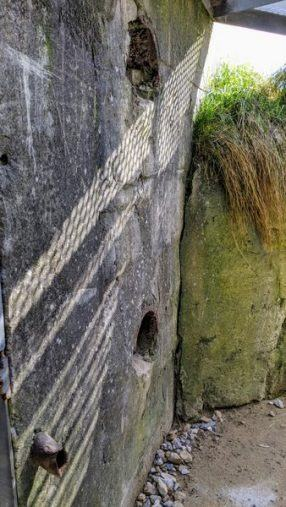 A pair of holes, one above the other, in a concrete wall