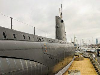 A view along the black hull of submarine HMS Alliance towards Portsmouth and the Spinnaker Tower in the distance the