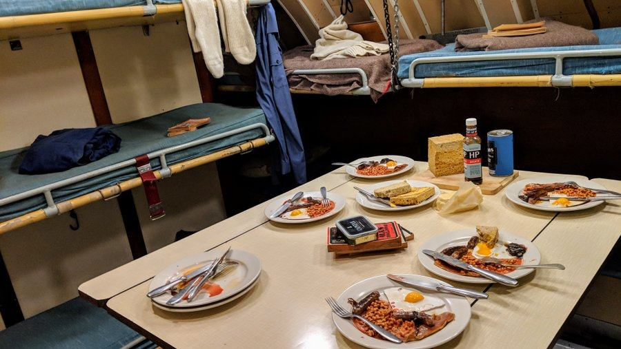 A table with plates of bacon & eggs in cramped crew quarters
