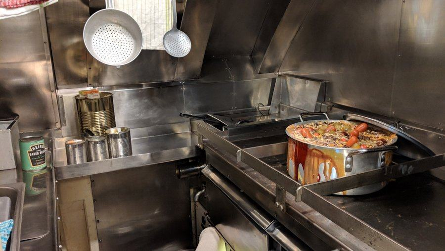 Stainless steel covered submarine galley with a huge pot of stew on the stovewith