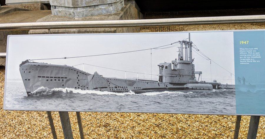 A display sign with a black & white photo of HMS Alliance in 1947