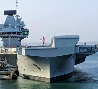 Royal Navy aircraft carrier, alongside in Portsmouth, viewed on a bright sunny day from the bow