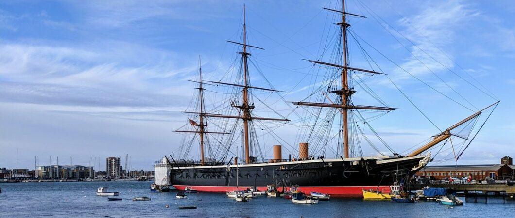 Three masted, black hulled warship with a red waterline