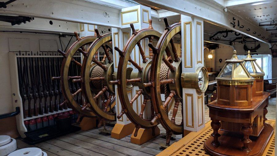 Four connected helmsmans wheels. Brass compass binnacles in the foreground, a rack of muskets on the back wall