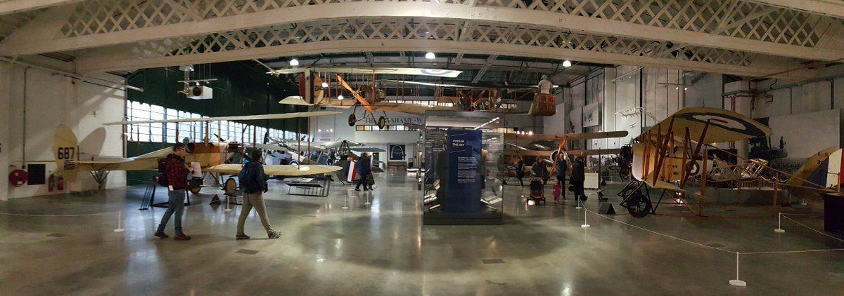 A hanger full of WW1 biplanes on the floor and suspended in the air.