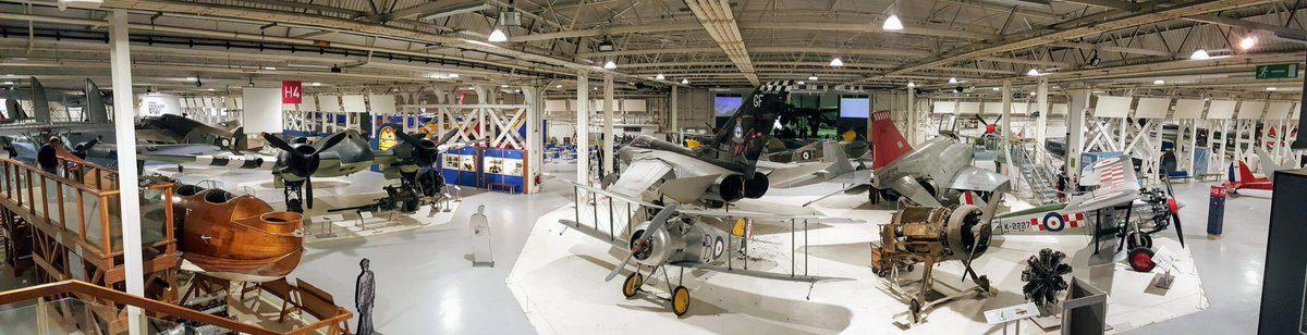 Wide shot from a high perspective of the middle of hanger 3, busy with multiple aircraft