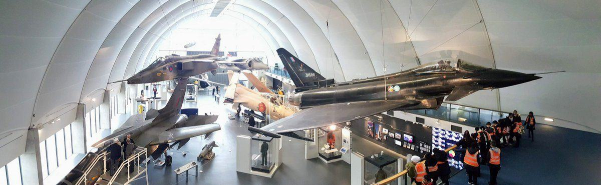 View looking down on large jet aircraft exhibited on the floor and suspended. There's a group of school children in hi-viz jackets looking on from a lower balcony.