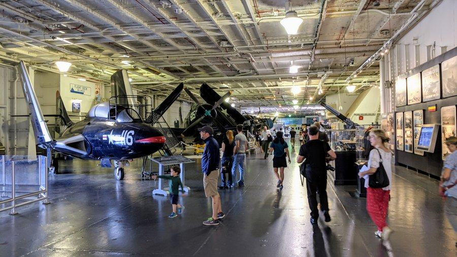 Visitors wander past an array of historic aircraft in the USS Yorktown's hanger