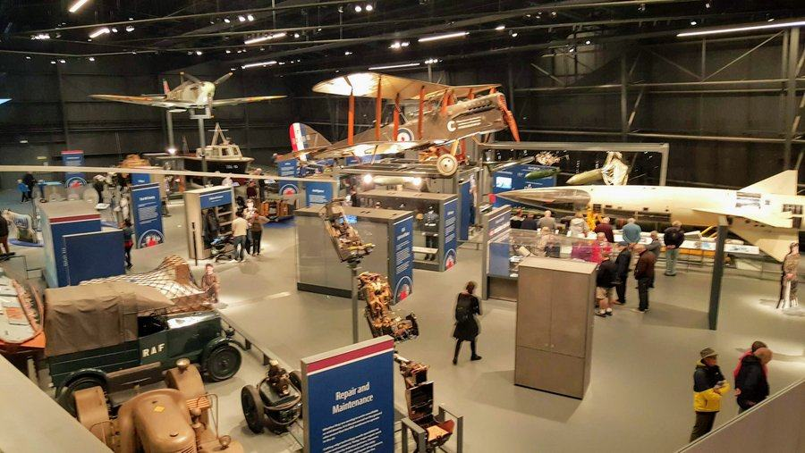 Photo taken from the balcony overlooking part of Hanger 1. There are  exhibits stands and vehicles and aircraft suspended above.