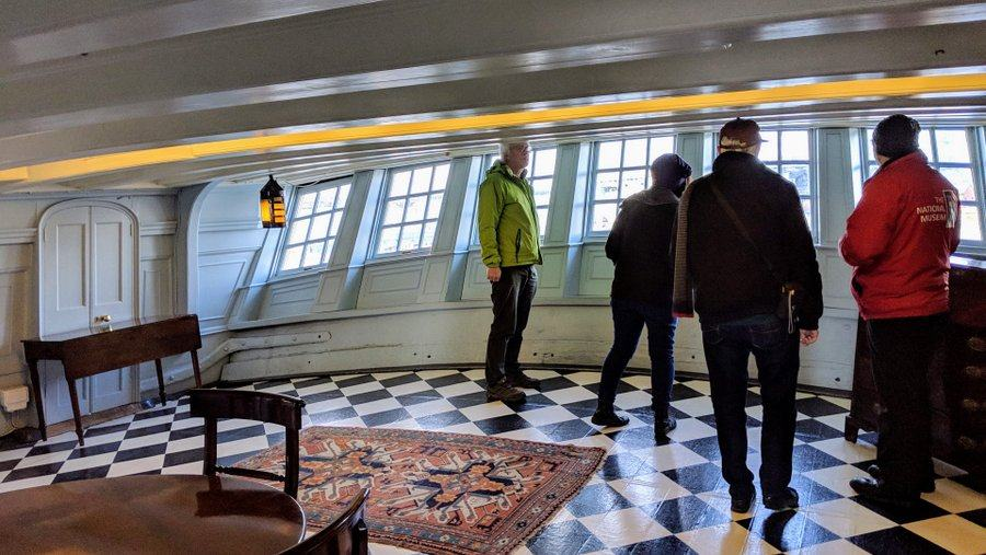 Visitors stand by the stern windows in a cabin with black & white chequered floor and light blue walls
