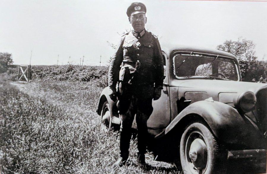 Black & white photo of Hauptmann Treiber in uniform standing next to his car