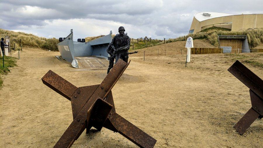 A rusty tank obstacle in the foreground. Behind it a statue of a soldier running out from a grey Higgins boat on the sand