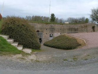 View of a partially hidden bunker with signage outside