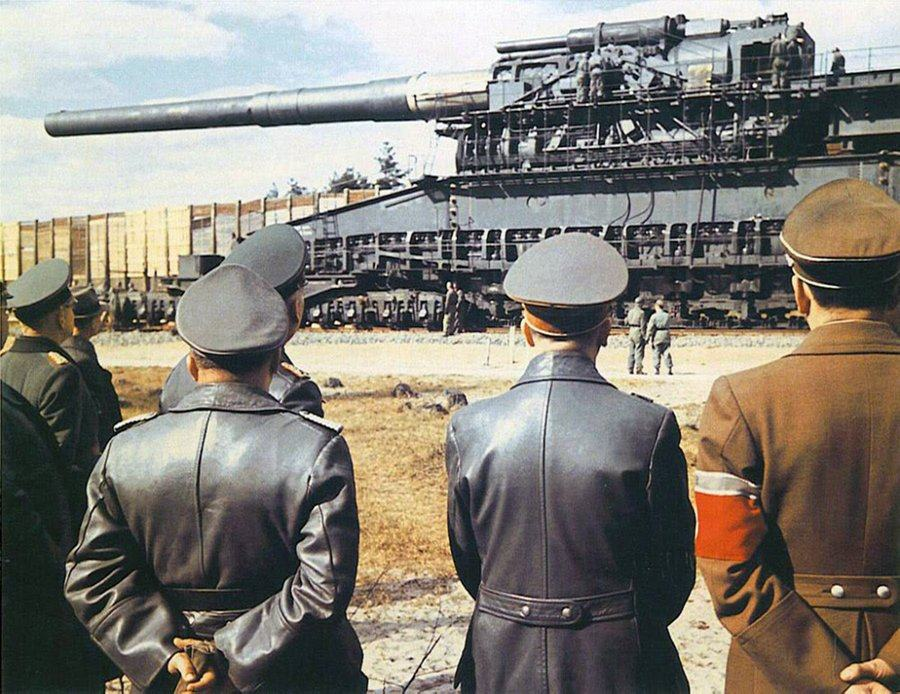 Colour photo of Hitler & Albert Speer in uniform with their backs to the camera, looking at a huge railway gun