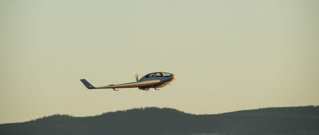 A thin flying wing flies in evening sunlight