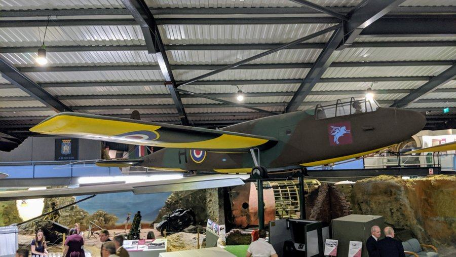 A large wooden glider in brown and green camouflage with yellow undersides, suspended from the museum roof