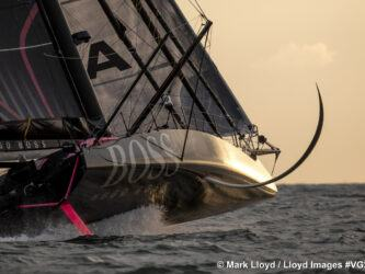 A black Vendee Globe racing yacht, Hugo Boss, heels over exposing her foils in the evening sunlight