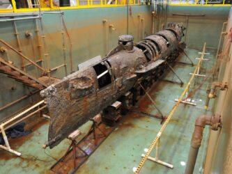The Hunley submarine looking brown & rusty with some panels missing rests in her tank without water