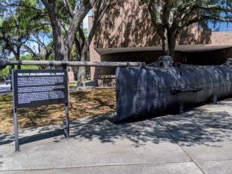 Small dark grey submarine sits under shady trees outside a museum