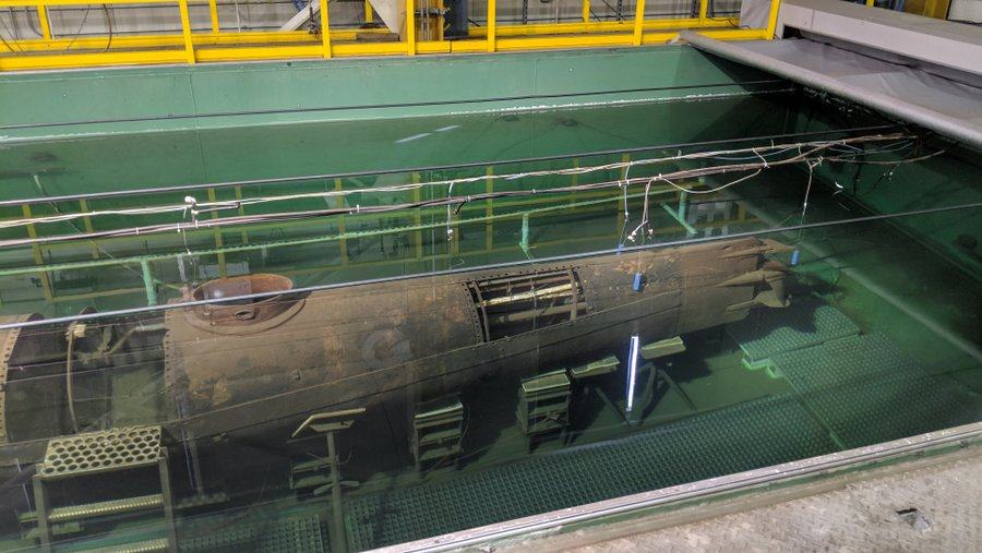 Submarine with hull sections removed lies under a chemical solution in a large tank