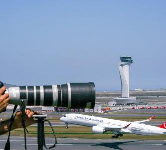 A camera with a telephoto lens overlooks a Turkish Airlines jet taking off at Istanbul Airport with the contral tower in the background