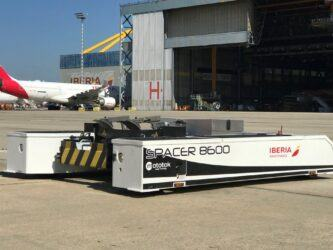 A white trolley-like aircraft tug sits on the tarmac new an Iberia airliner & hanger