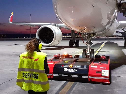 A woman operator in a hi-vis jacket uses a remote-control tug to push back an Iberia airliner