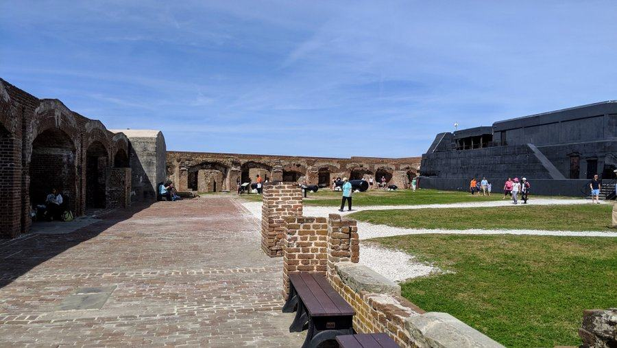 Fortress courtyard on a sunny day with walls surrounding a grassy area