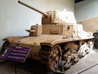 Old fashioned medium tank with riveted armour and painted in light brown desert camouflage