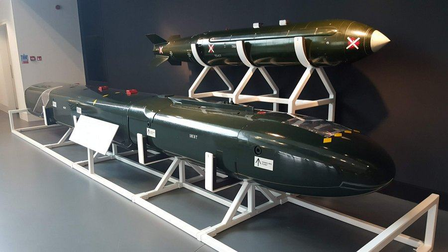 A long green sled-like box that looks a bit like a car roof box, and displayed above it a large sleek green nuclear bomb