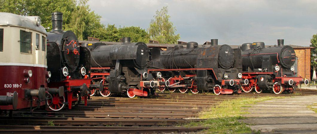 Old black & slightly rusty steam engines in a circle on tracks around a turntable