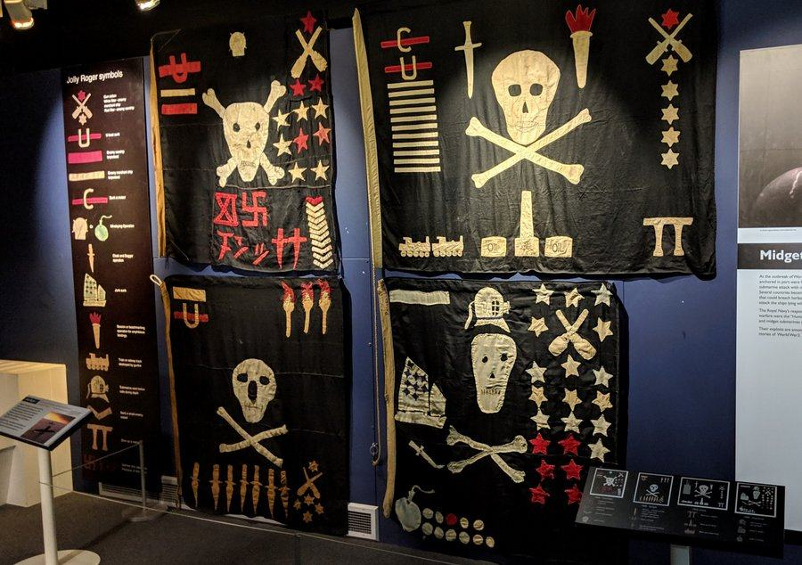 Four homemade skull & crossbones flags with other symbols on them