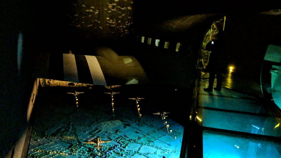 View from a glass walkway looking down on C-47 transport aircraft dropping paratroops over a moonlit nightscape