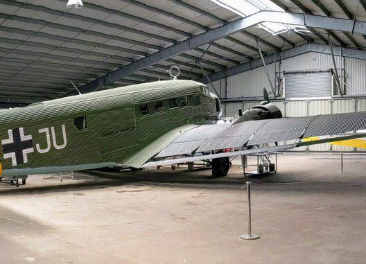 A three engined Junkers 52 transport aircraft in Luftwaffe colours, dark green and yellow, parked in a large hanger at the Salis Flying Museum