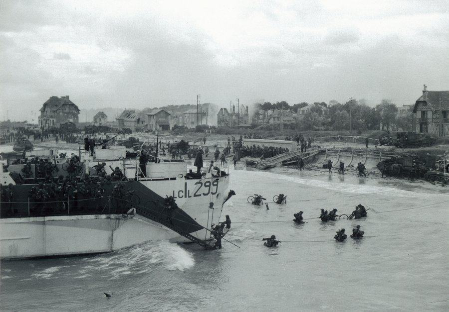 Black & white photo of Canadian soldiers disembarking from landing ships onto a narrow beach