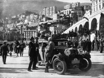 A black & white photo of Kitty Brunell's Talbot car parked on the quayside at Monte Carlo. She is leaning over the open roof talking to three men in suits.