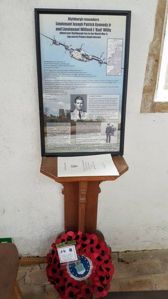 Information board and wreath on a stand inside Blythbrugh church