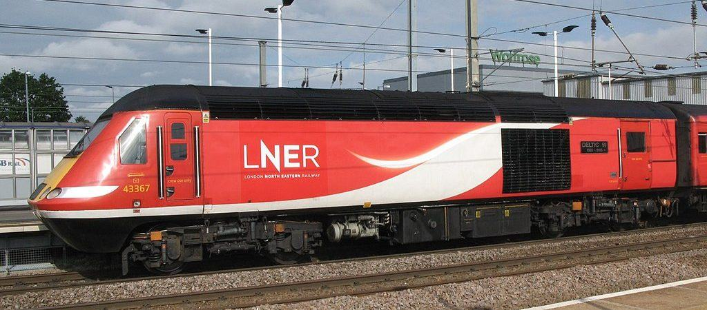 A red high speed diesel locomotive with LNER logo stands alongside a platform