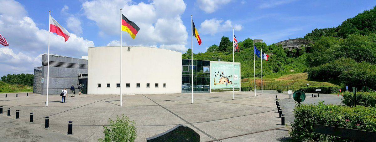 Entrance building on a sunny day with flags outside and the dome itself in the background