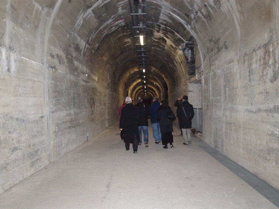 A group walking down a large grey dusty tunnel