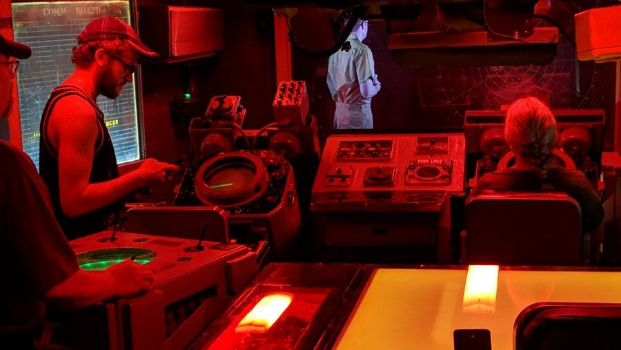 Radar screen and consoles in a red light with a simulated officer projected on a glass screen