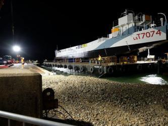 Worklights illuminate the Tank Landing Craft on her barge alongside a shingle beach