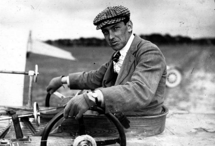 Black and white close-up of Latham in jacket, tie and with a cap, in his aircraft