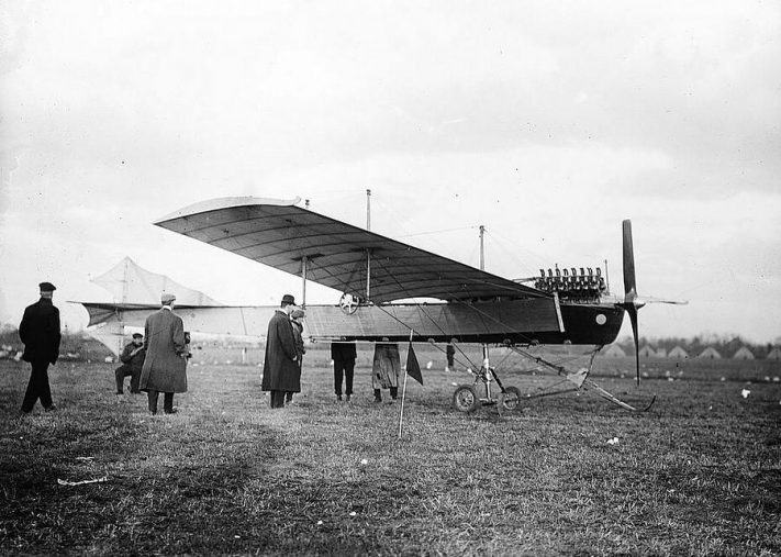 Black & white photo of men in coats, caps & hats, standing around a monoplane in a field