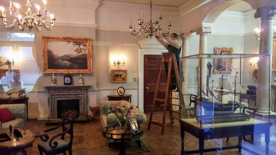 Model drawing room with a servant on a step ladder cleaning the chandelier