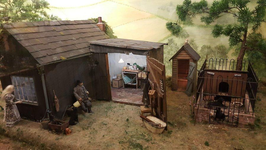 Model scene with a labourer leaning against his house. His workshop door is open and his dogs are in the kennel nearby.