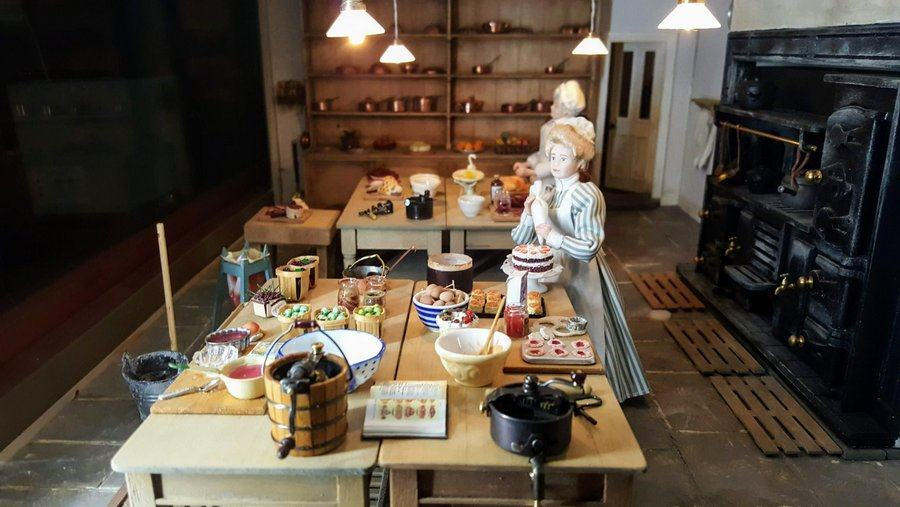model kitchen scene with a female cook standing over a table groaning with jam tarts, pastries, apples and other produce