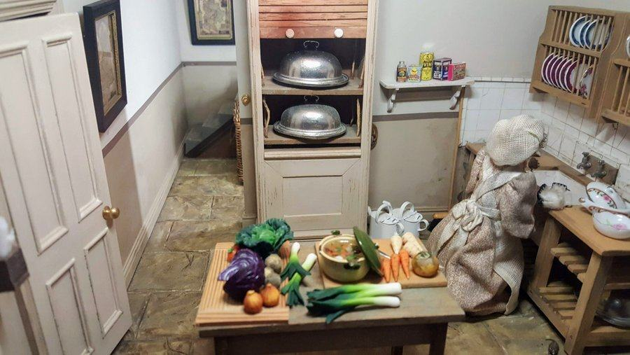 Model scene of a country house pantry with a servant kneeling to get something out from under the sink. Behind her is a table full of vegetables.